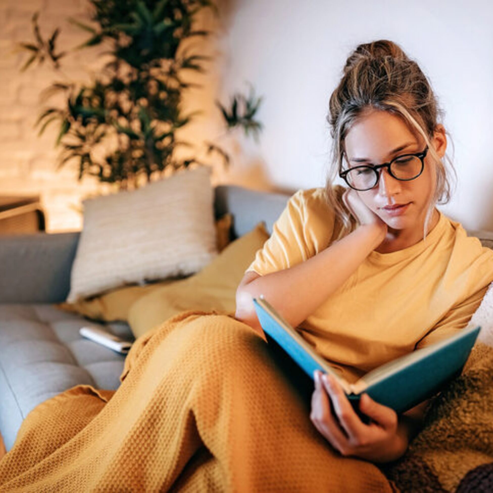 Frau liest Buch in gemütlichem Wohnzimmer