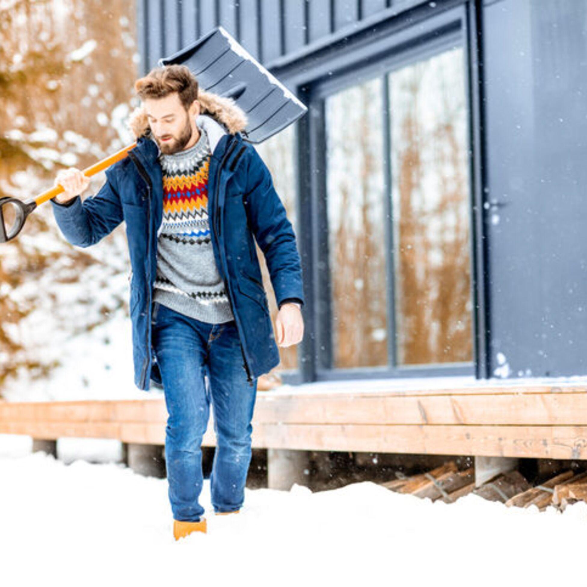 Mann mit Schneeschaufel geht durch den Schnee