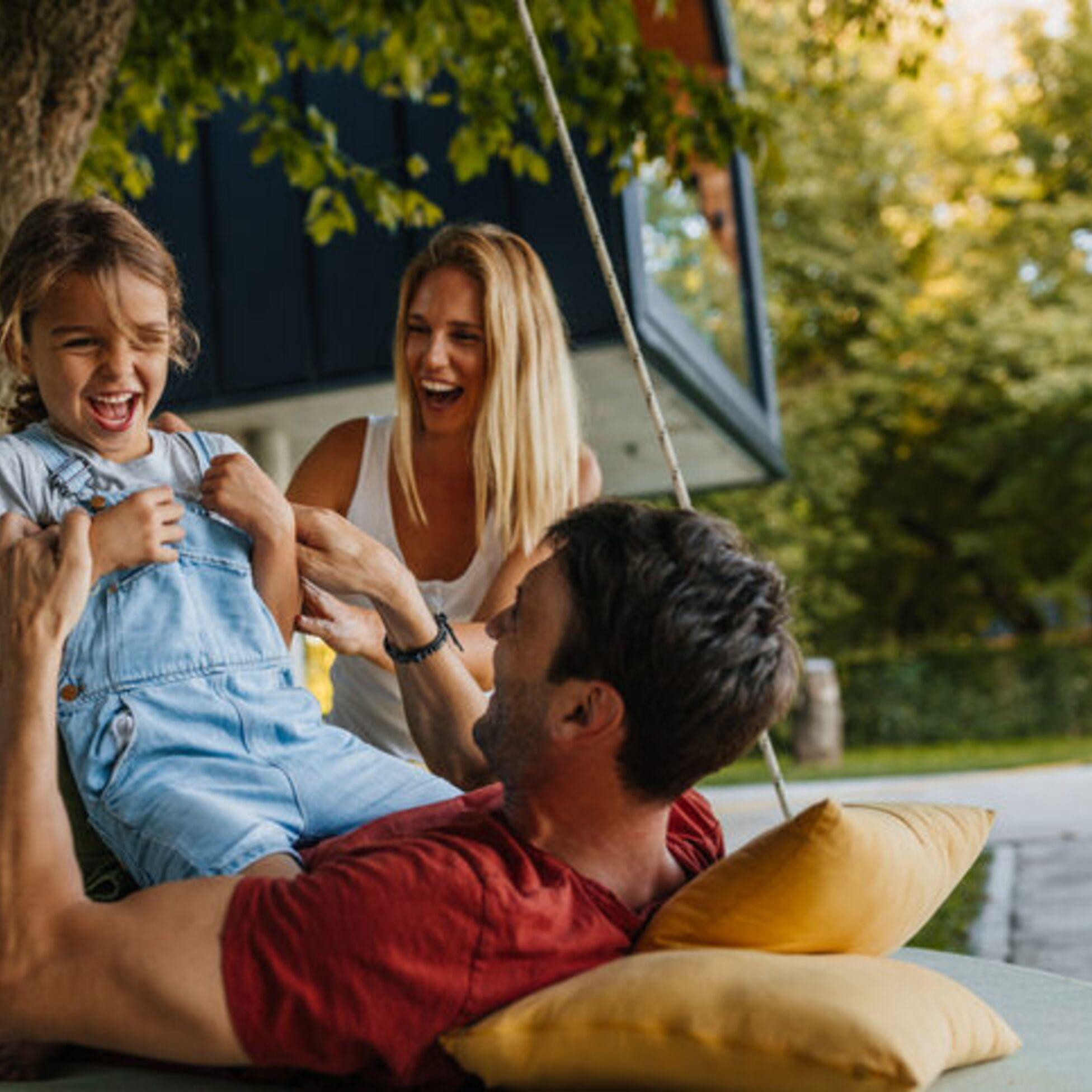 Eltern spielen mit ihrem Kind im Garten vor dem Haus