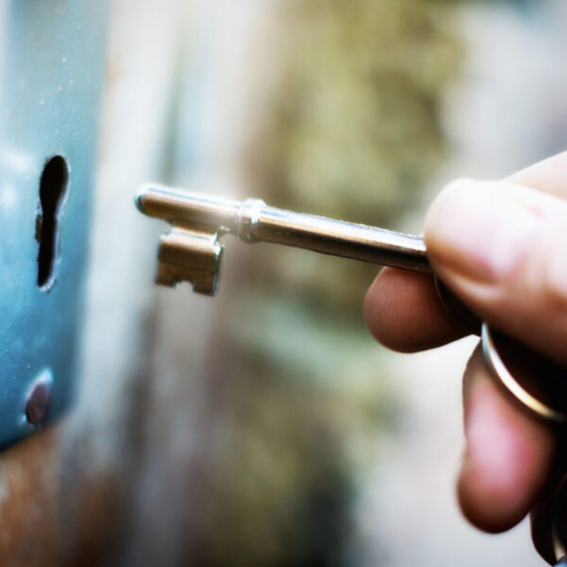 Hand steckt Schlüssel in Schloss