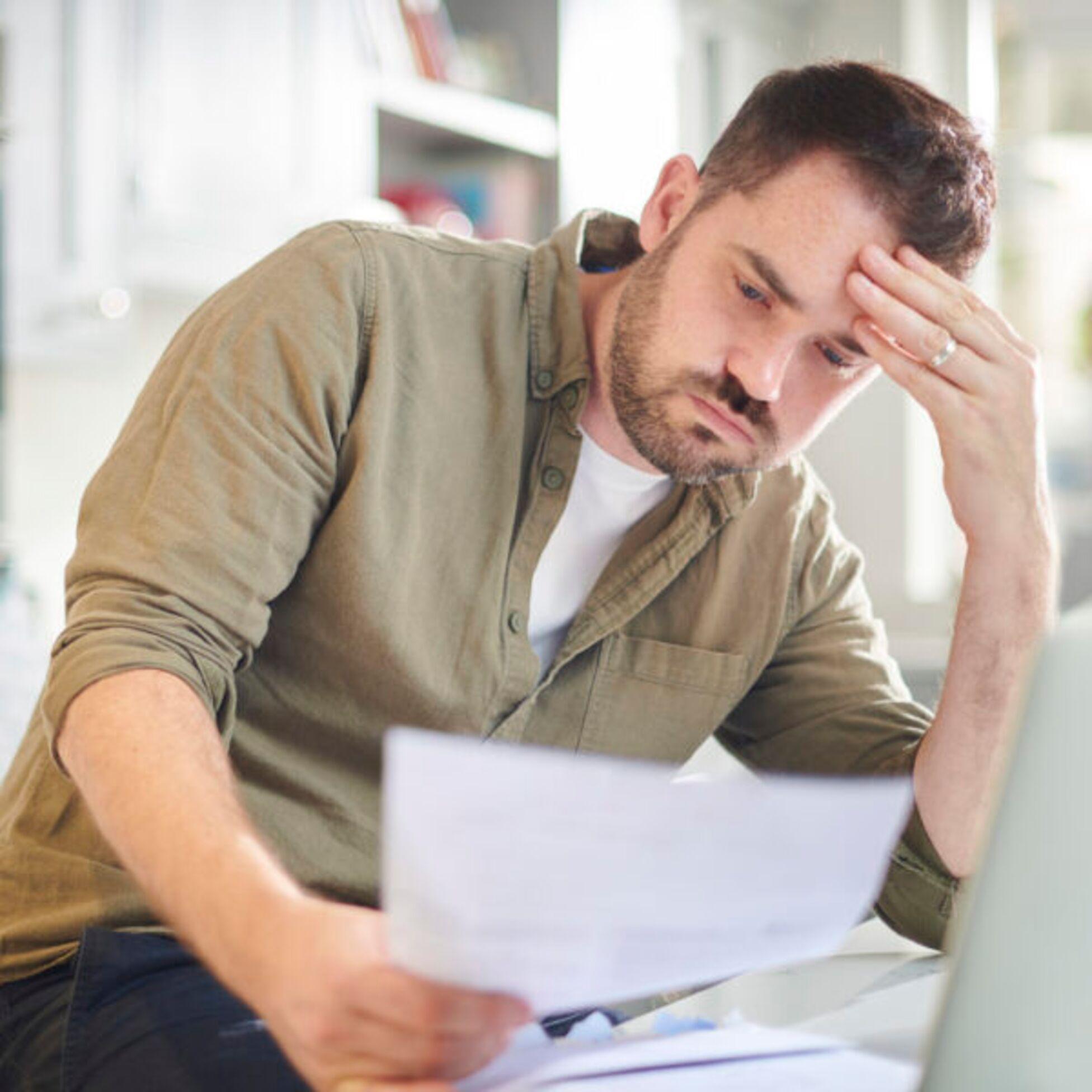 Besorgter Mann blickt auf einen Brief