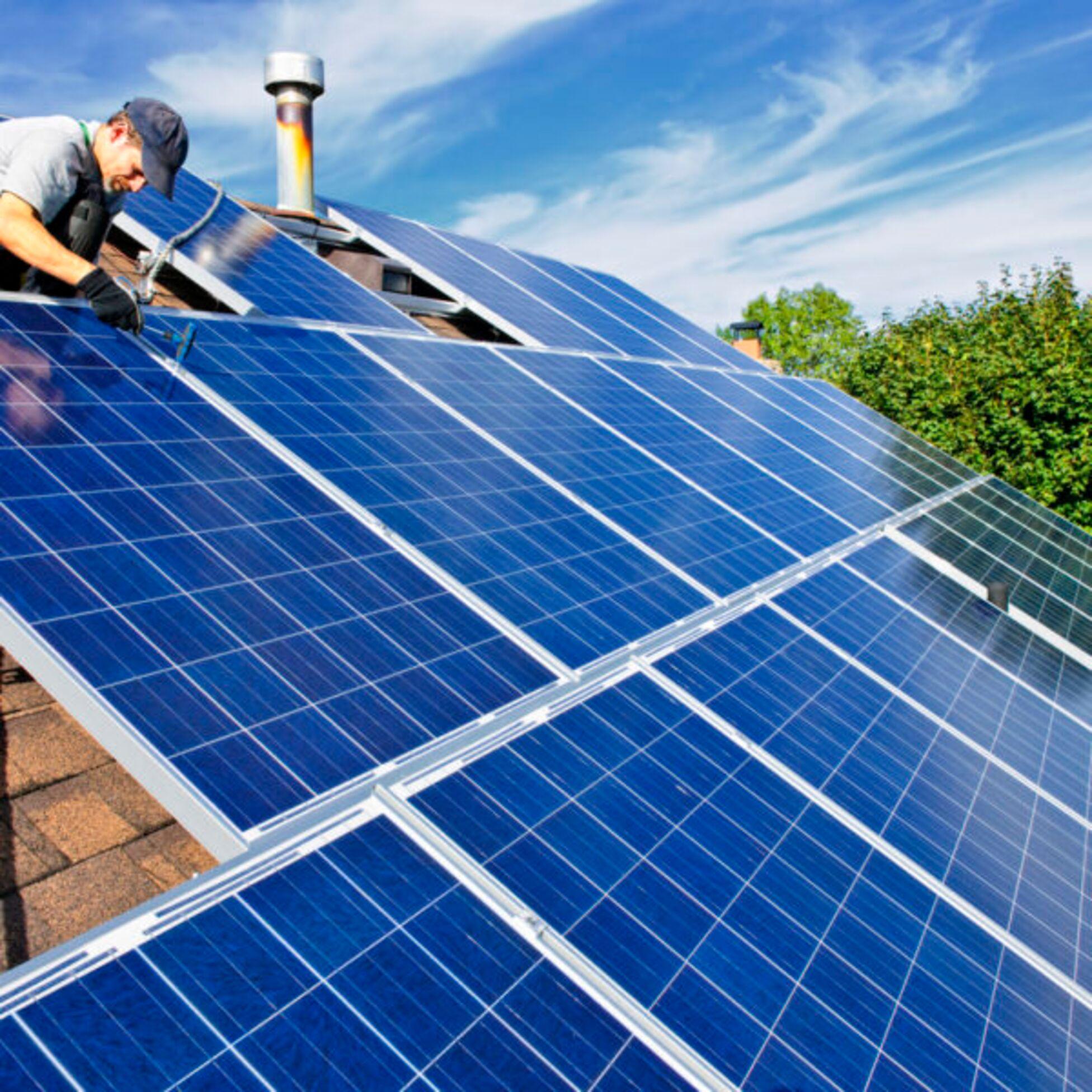 Mann installiert Solaranlage auf Hausdach