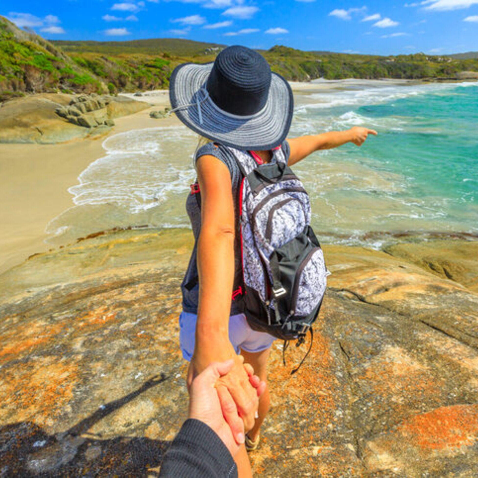Junge Frau zeigt auf Strand und Meer in Australien