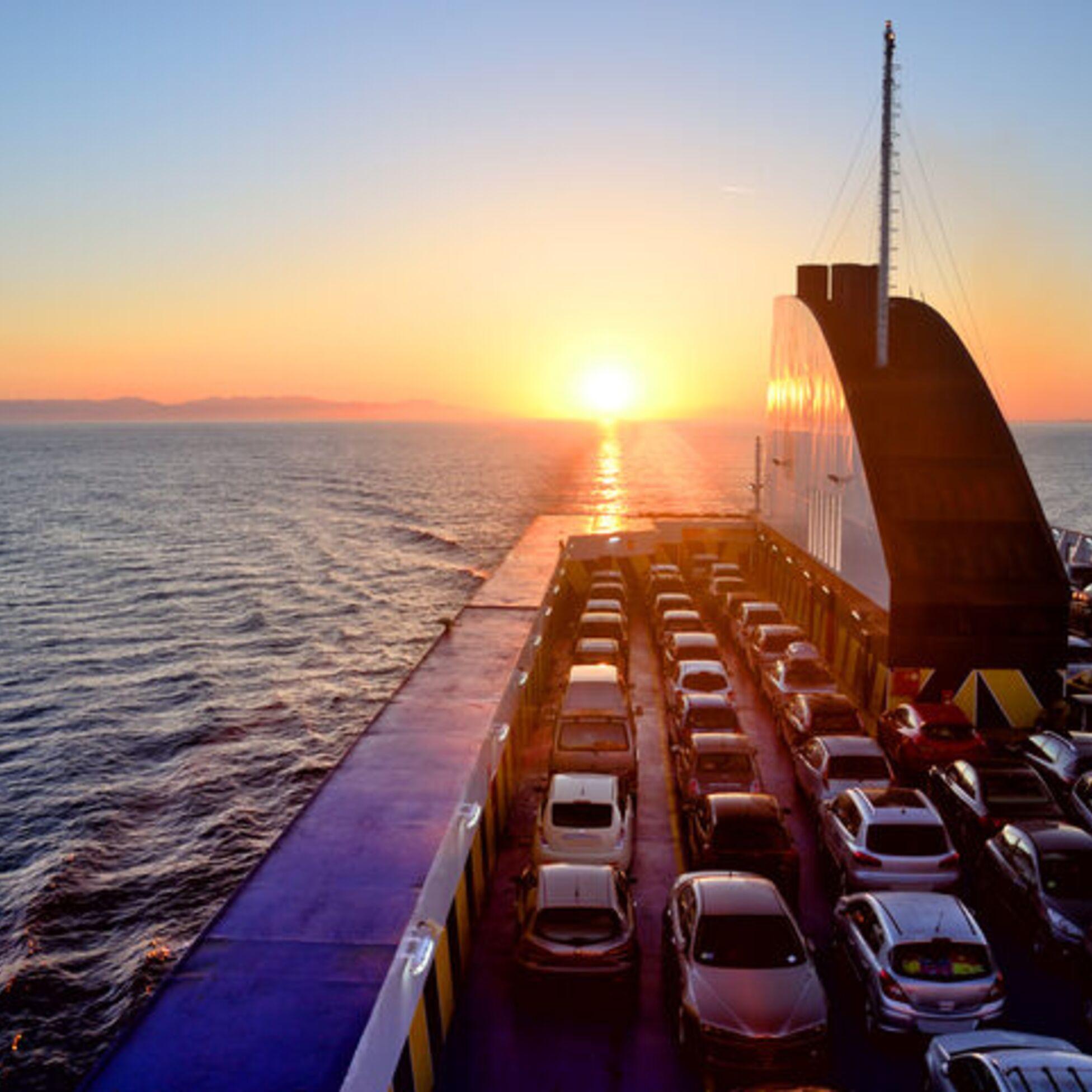 Fähre mit Autos auf See bei Sonnenuntergang