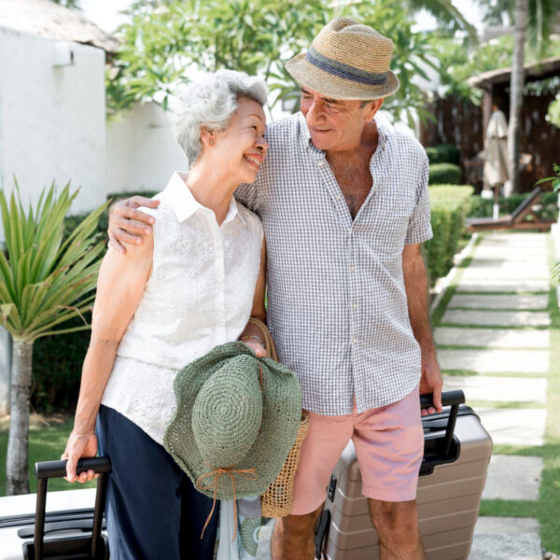Rentner beim Auswandern: Frau und Mann mit Koffern