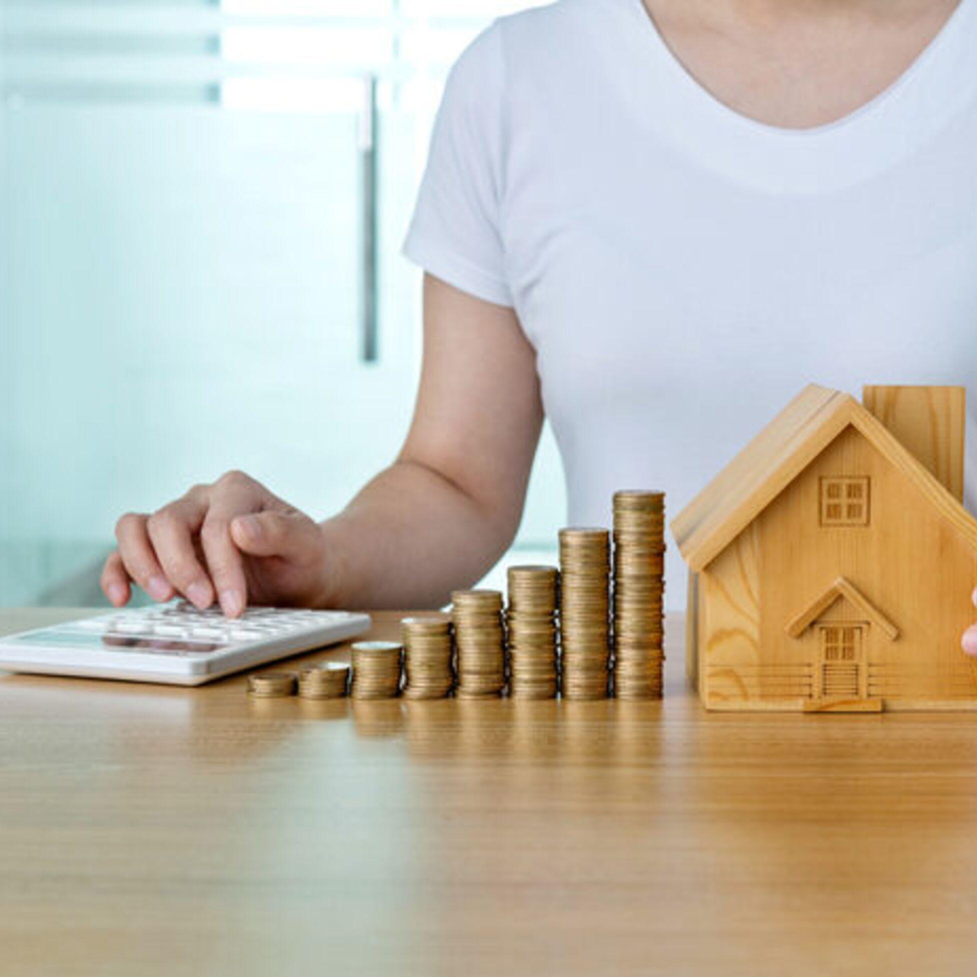Frau berechnet Kosten für Hausbau