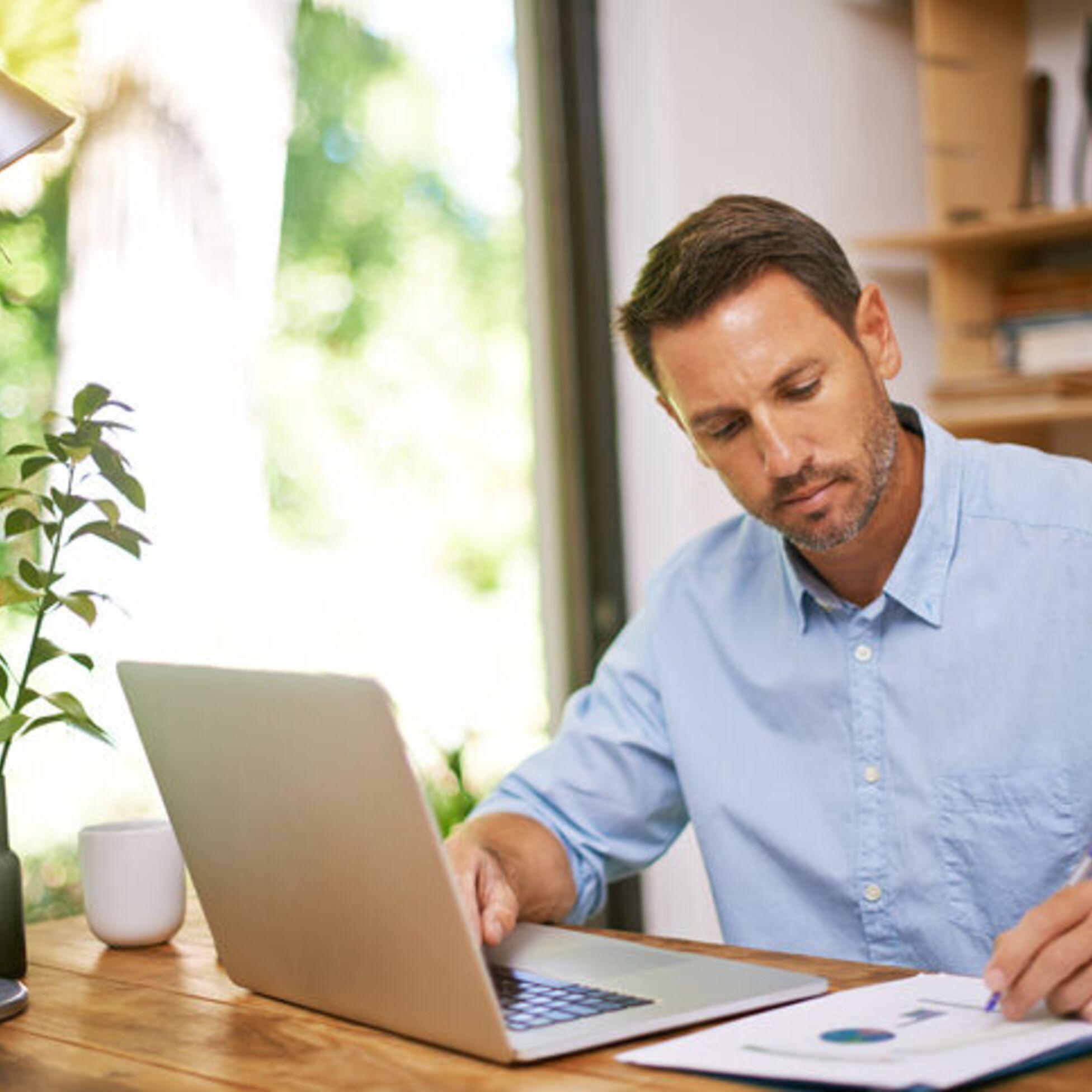 Mann prüft Unterlagen am Schreibtisch