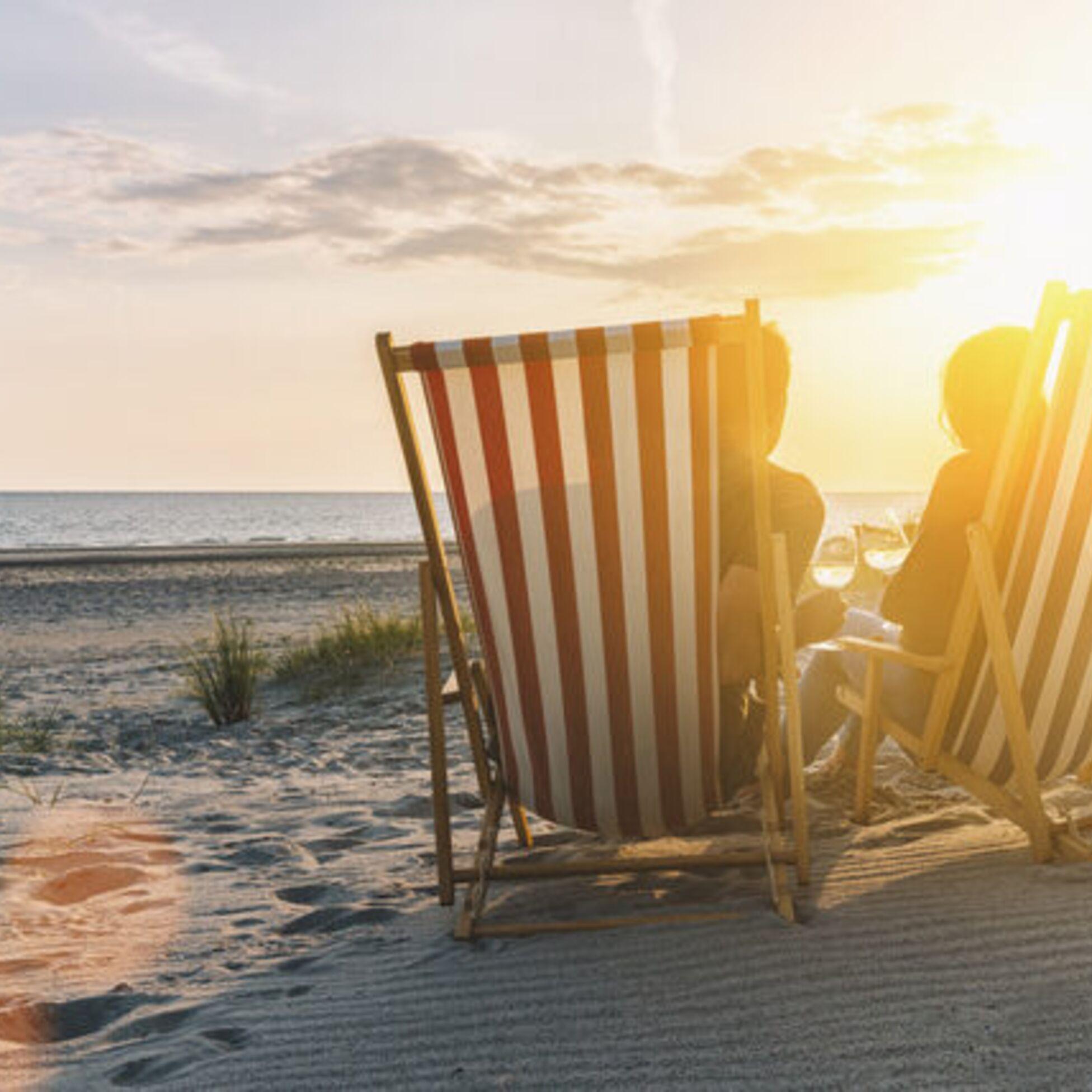 Paar sitzt in Liegestühlen am Strand