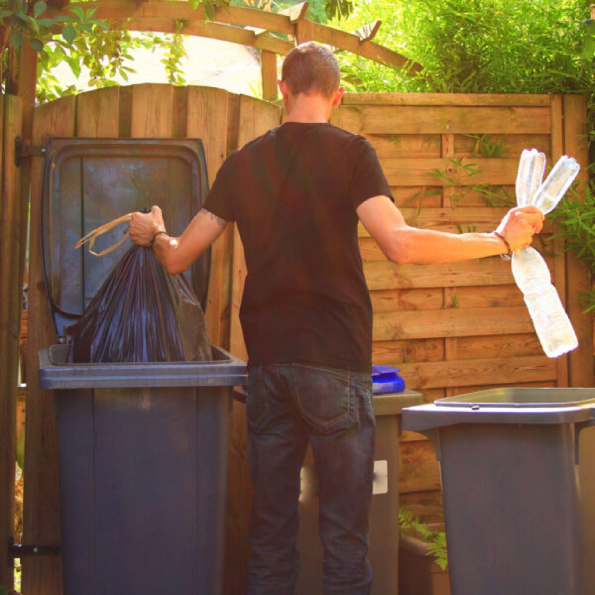 Mann sortiert Müll in Tonnen