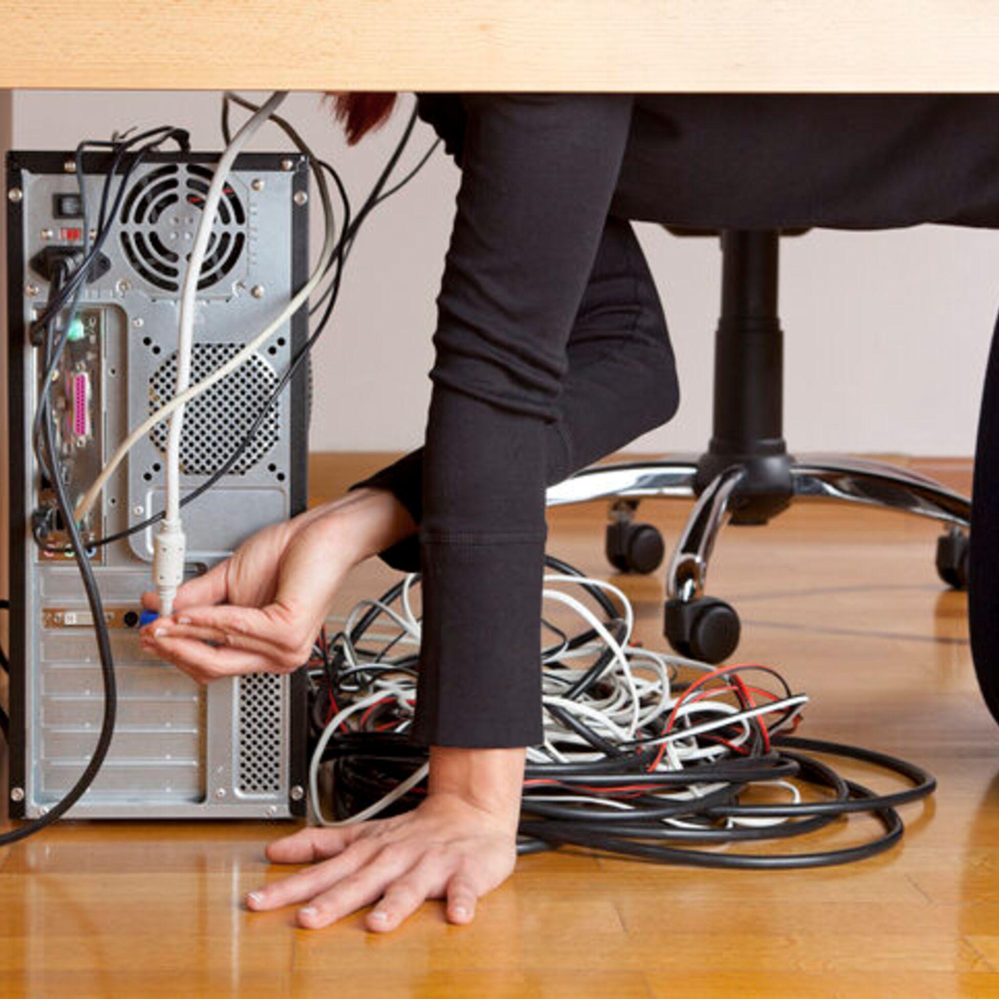 Frau steckt Kabel in PC