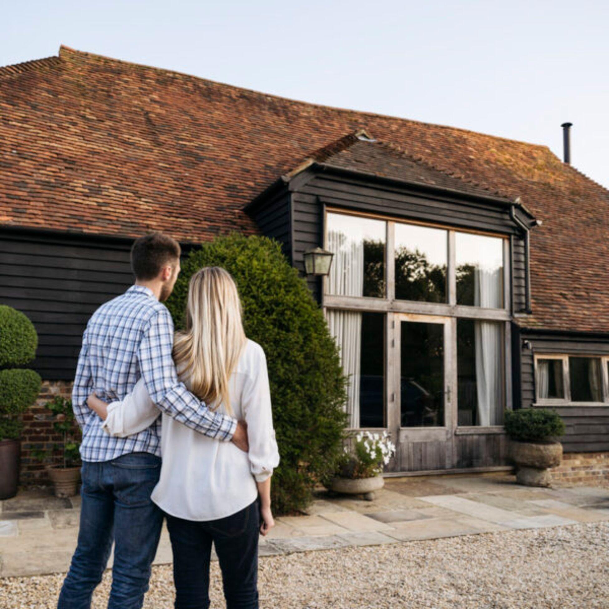 Junges Paar steht vor Haus