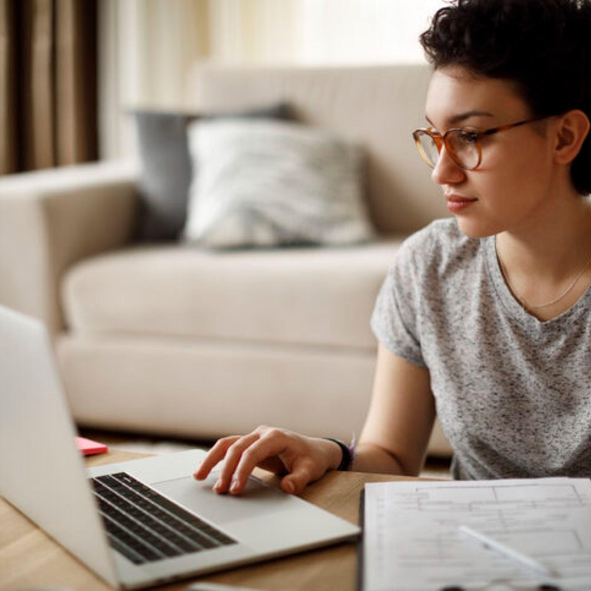Frau arbeitet am Laptop und organisiert Unterlagen