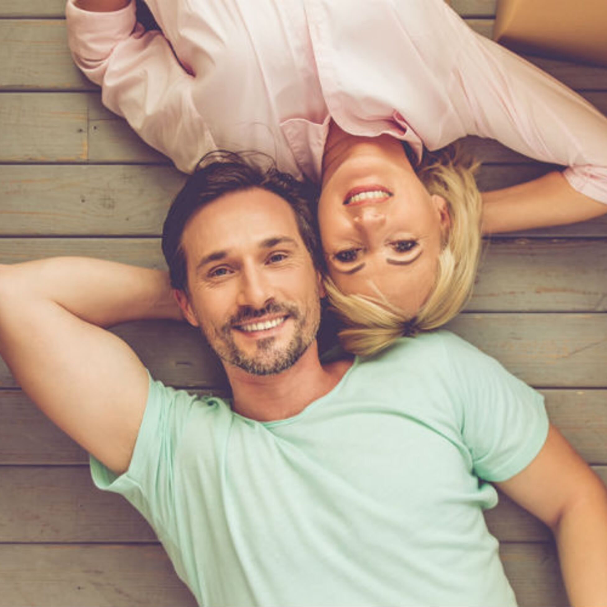 Mann und Frau liegen zwischen Umzugskartons auf dem Fußboden und schauen lächelnd nach oben