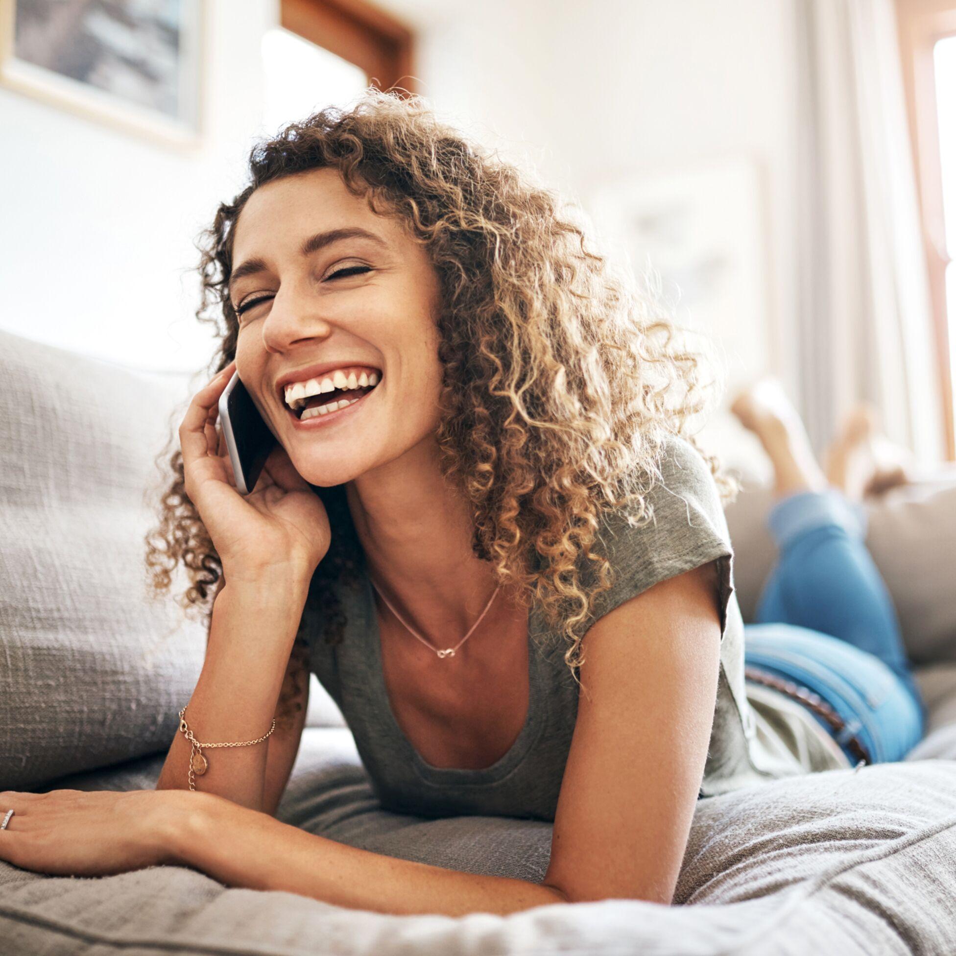 Frau mit Smartphone telefoniert glücklich