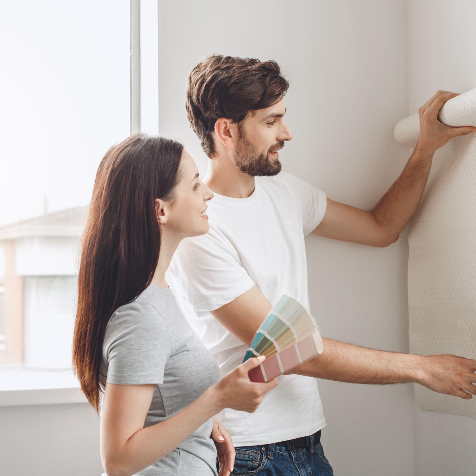 Junges Paar tapeziert Wohnung
