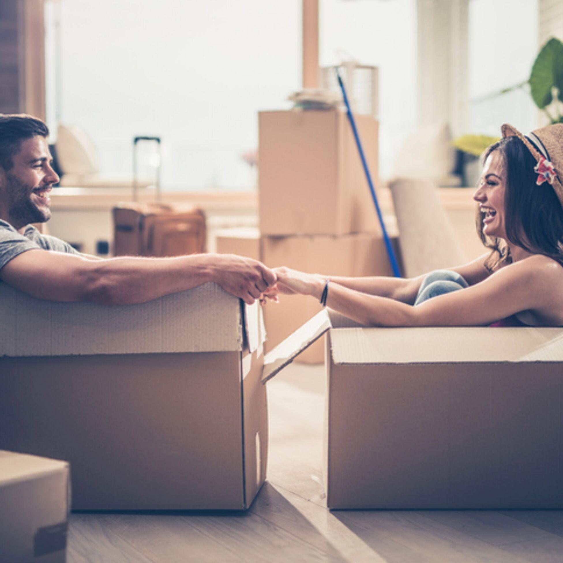 Paar sitzt in Kartons und hält Händchen