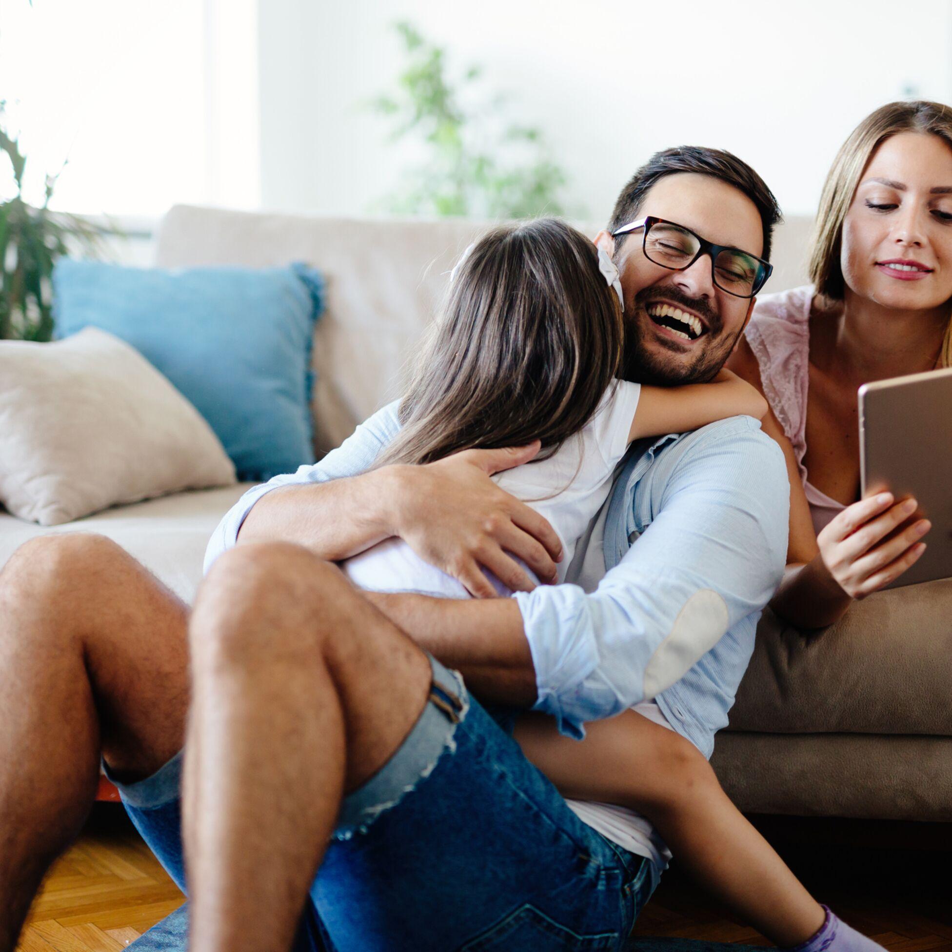 Eltern und Tochter auf der Couch, Mutter hält Tablet-PC in der Hand