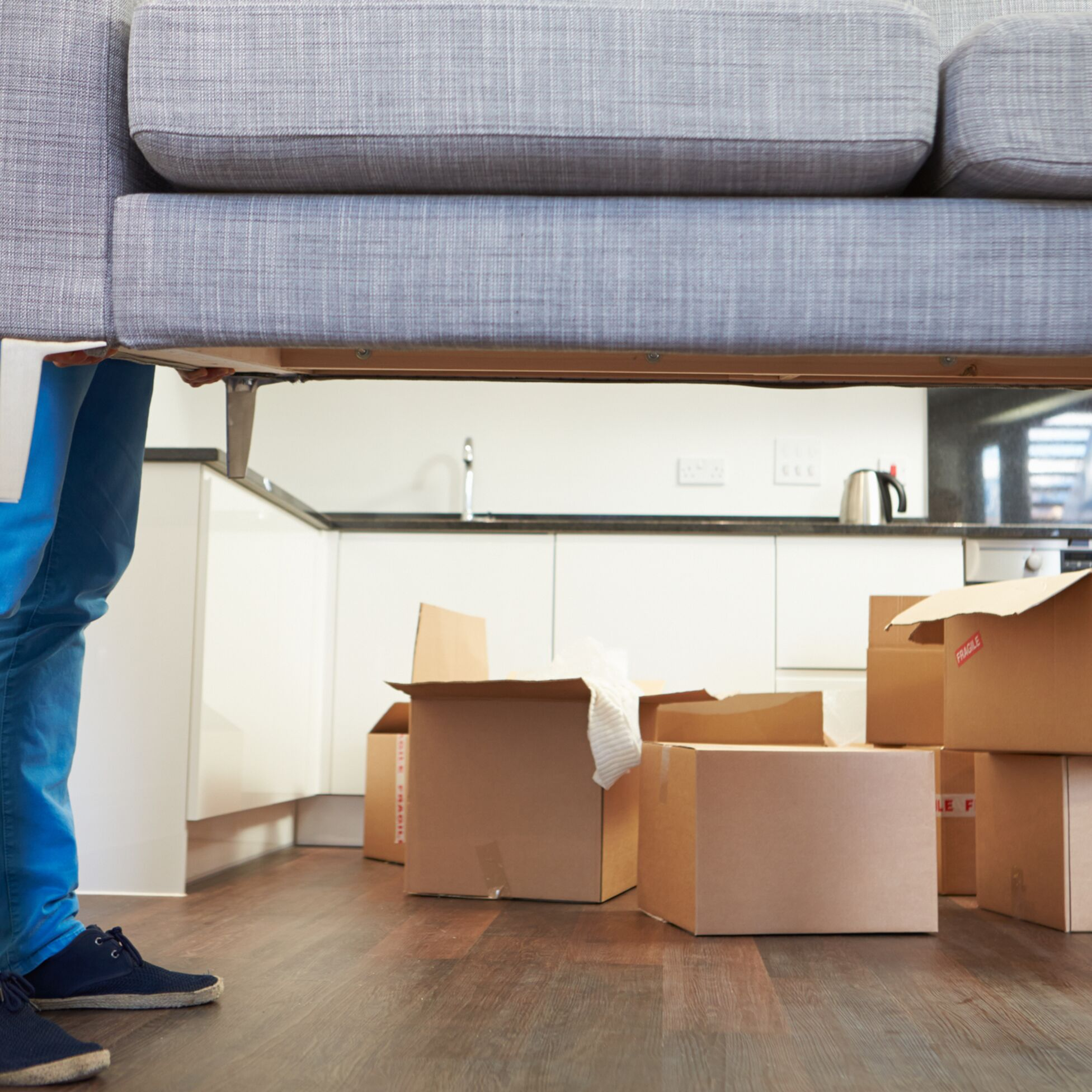 Umzugshelfer tragen Sofa aus der Wohnung im Hintergrund stehen Umzugskartons