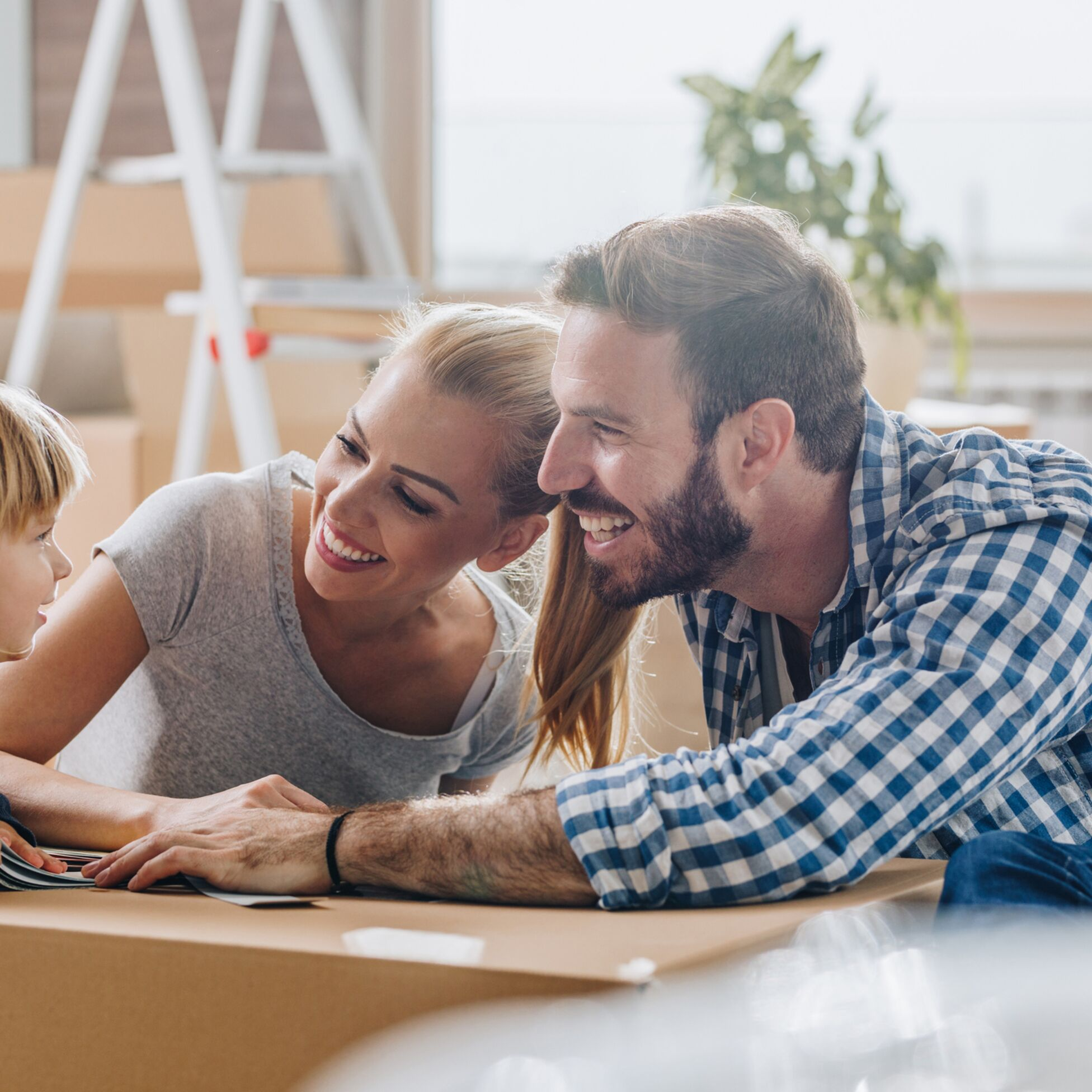 Eltern und Sohn zwischen Umzugskartons in neuer Wohnung