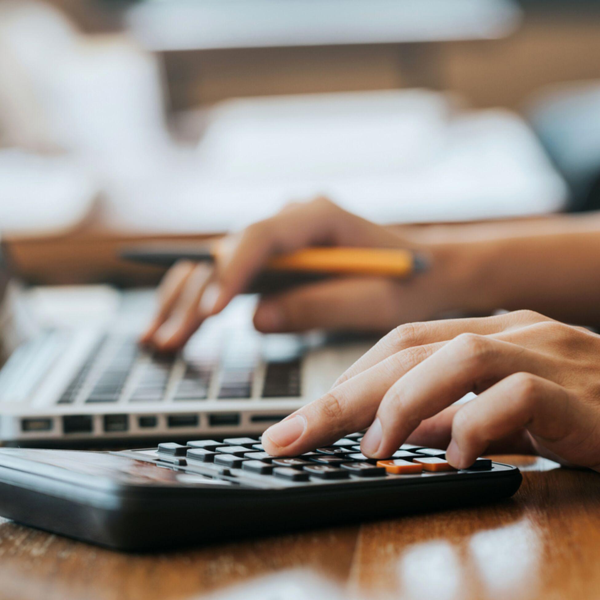 Hand an Taschenrechner berechnet Höhe Mietkaution