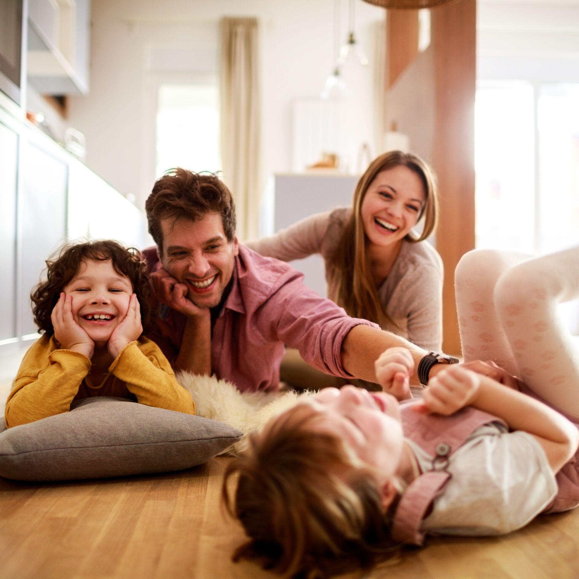 Junge Familie spielend und lachend auf dem Boden ihrer Wohnung