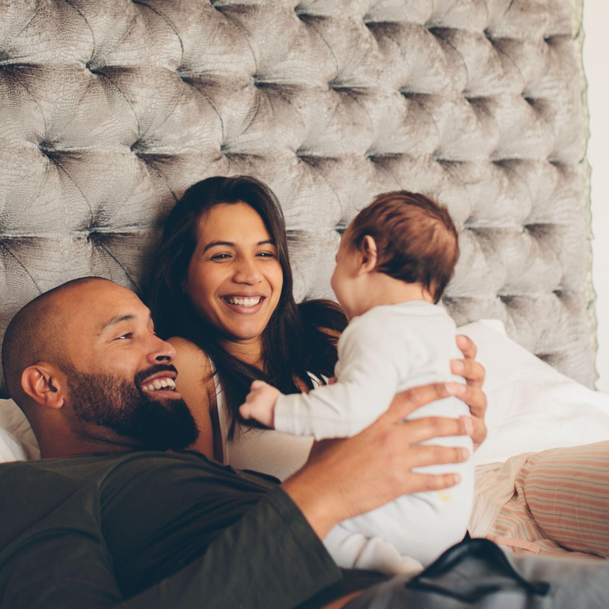 Familie mit Kleinkind im Bett