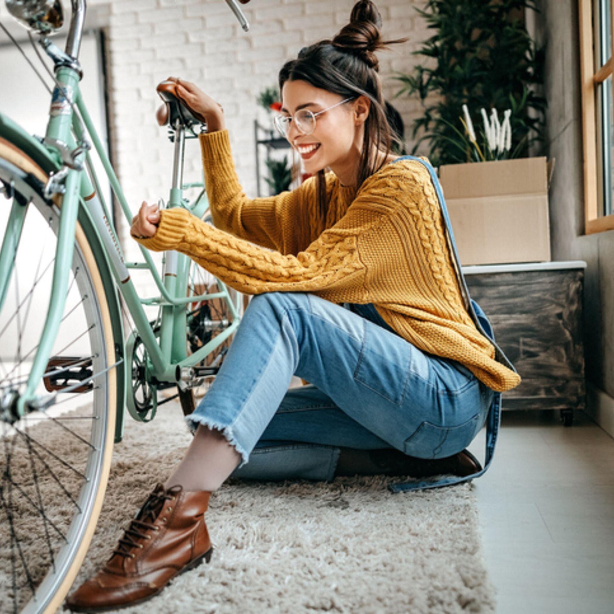 Junge Frau mit Fahrrad in neuer Wohnung