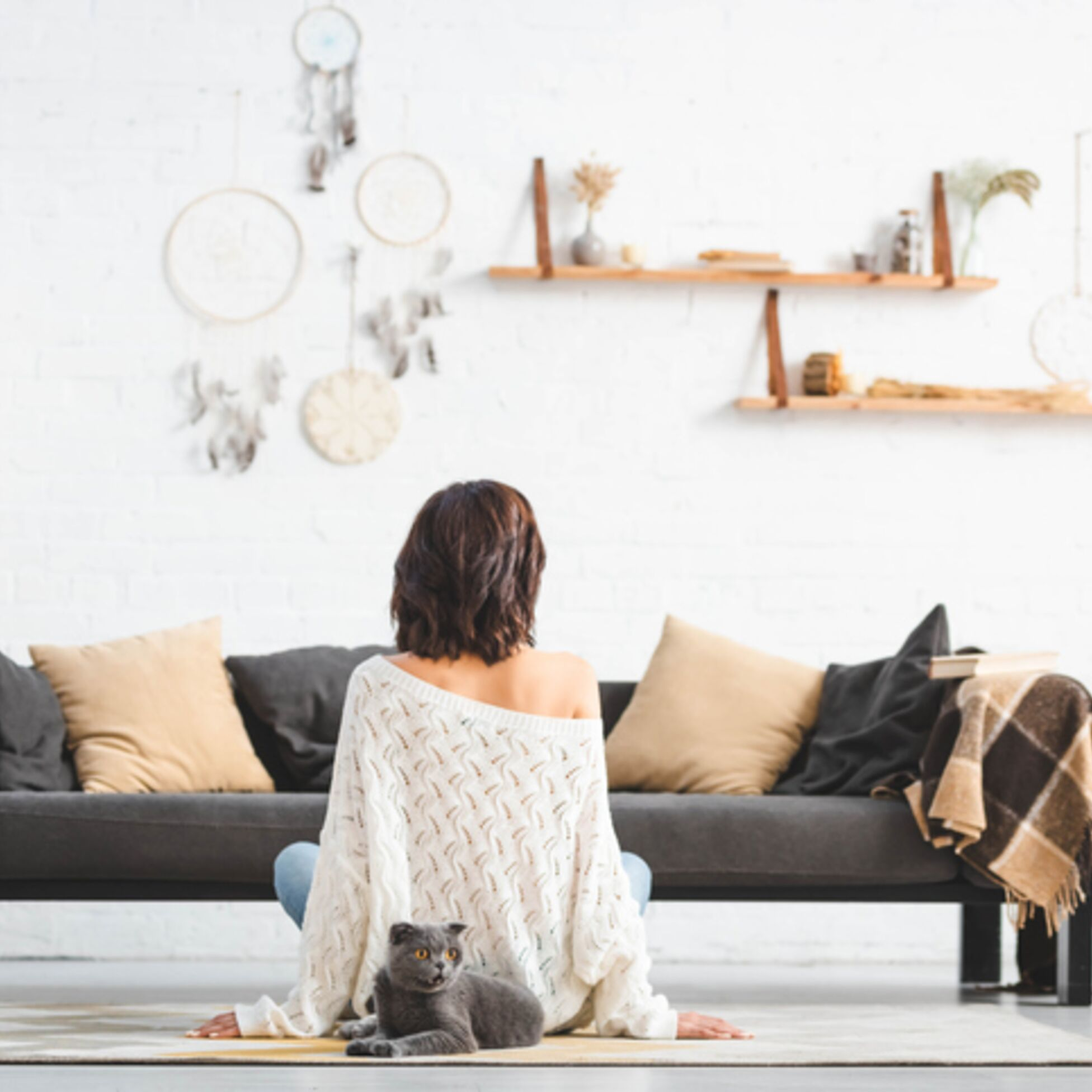 Frau sitzt in minimalistischem Wohnzimmer