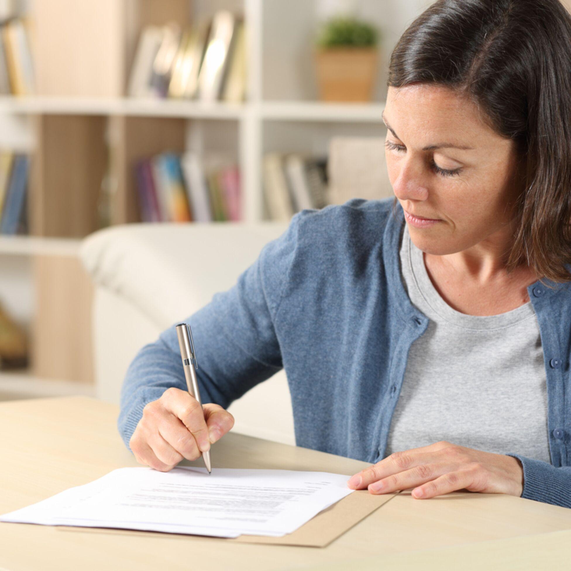 Frau schreibt am Tisch
