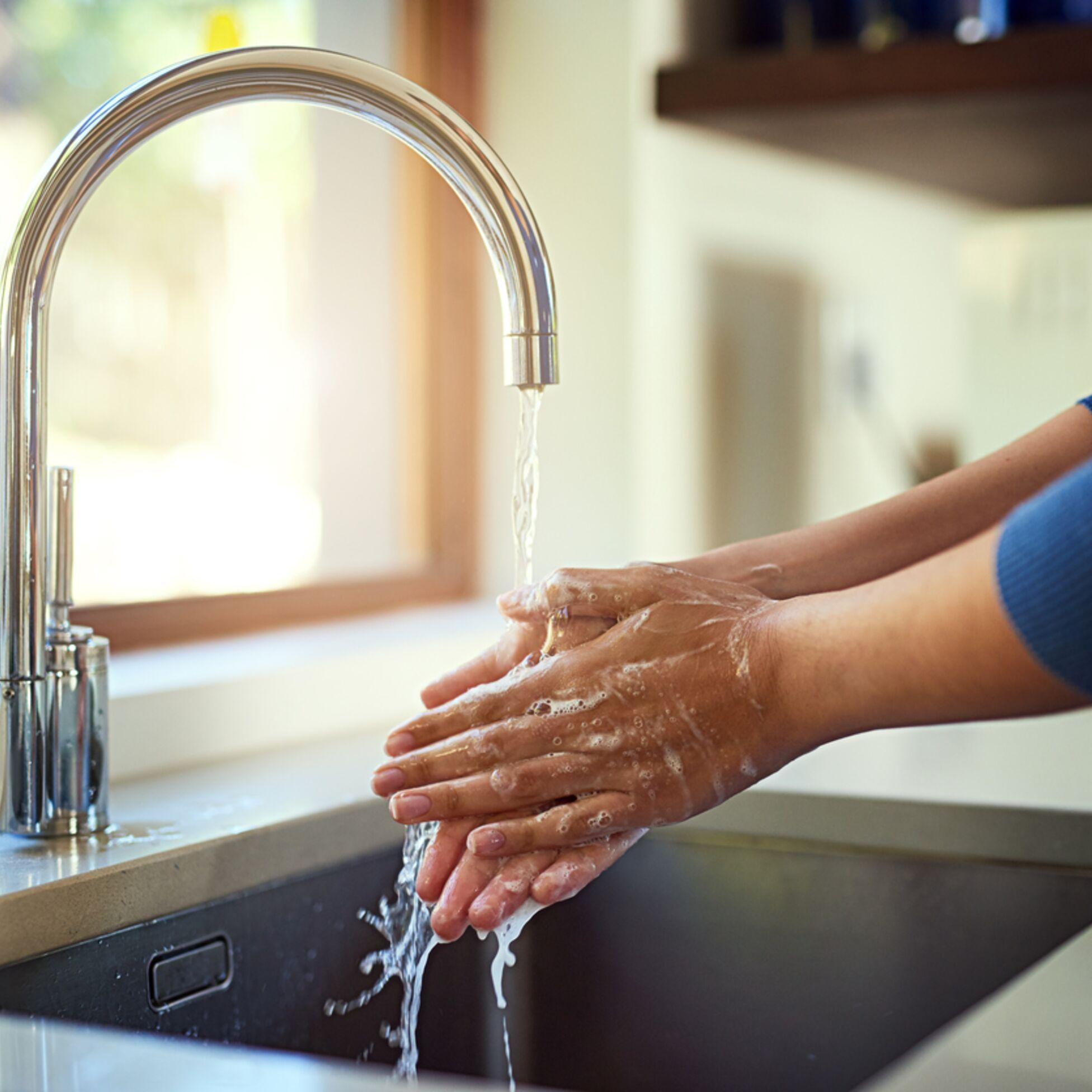 Frau wascht Hände unter Wasserhahn