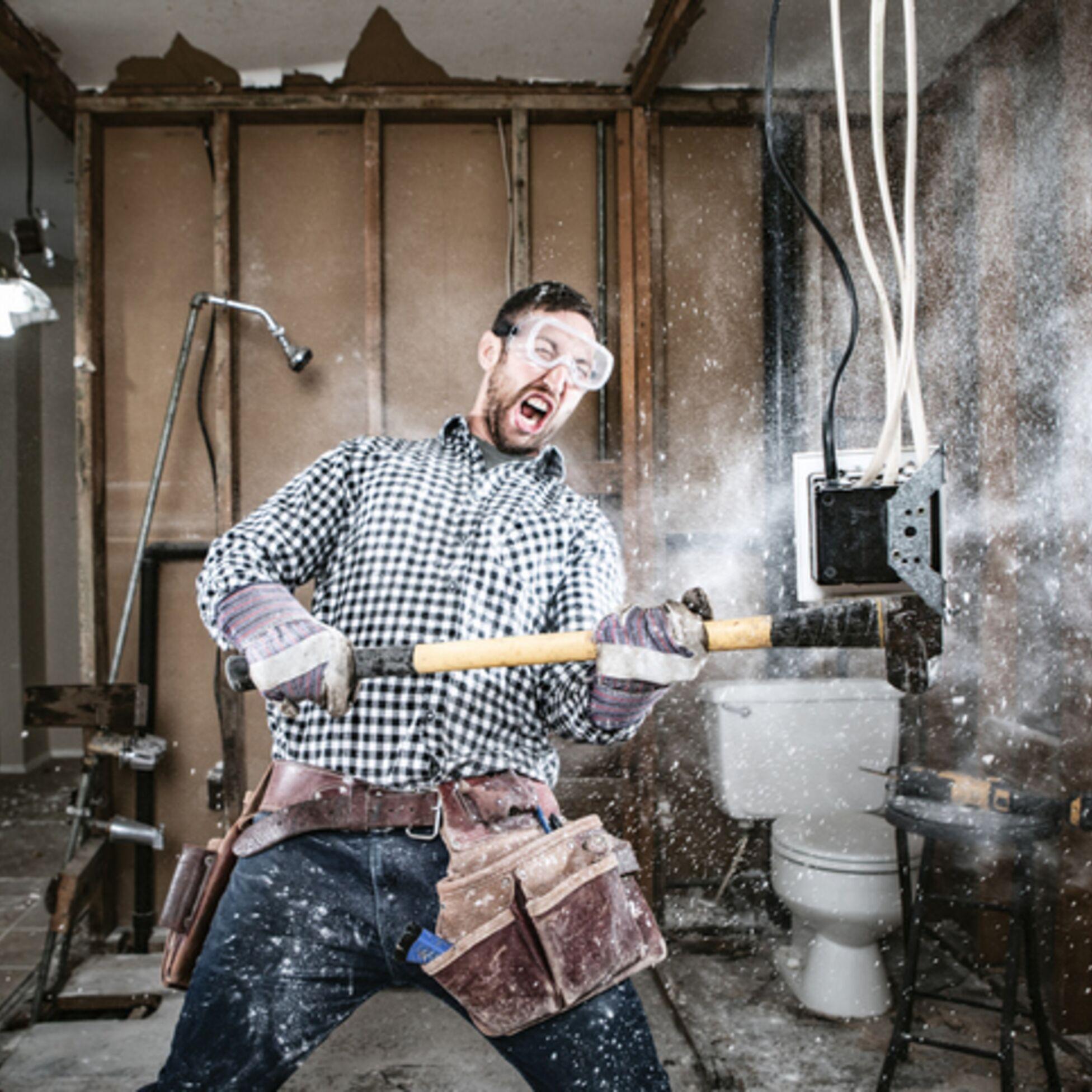 Man schlägt mit dem Vorschlaghammer Wand kaputt