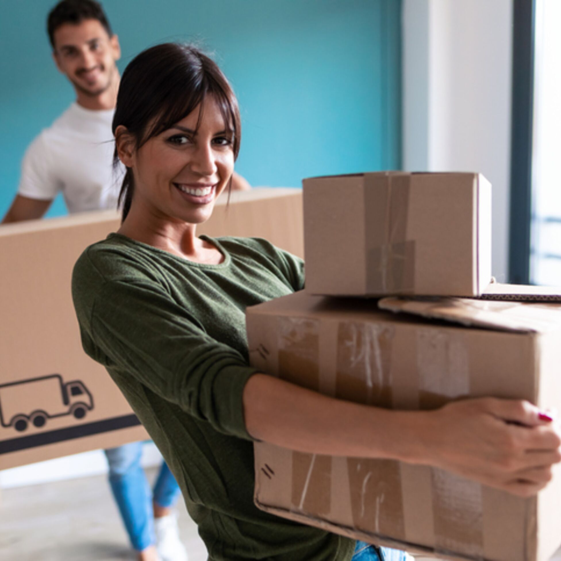 Junges Paar trägt Umzugskartons in die neue Wohnung
