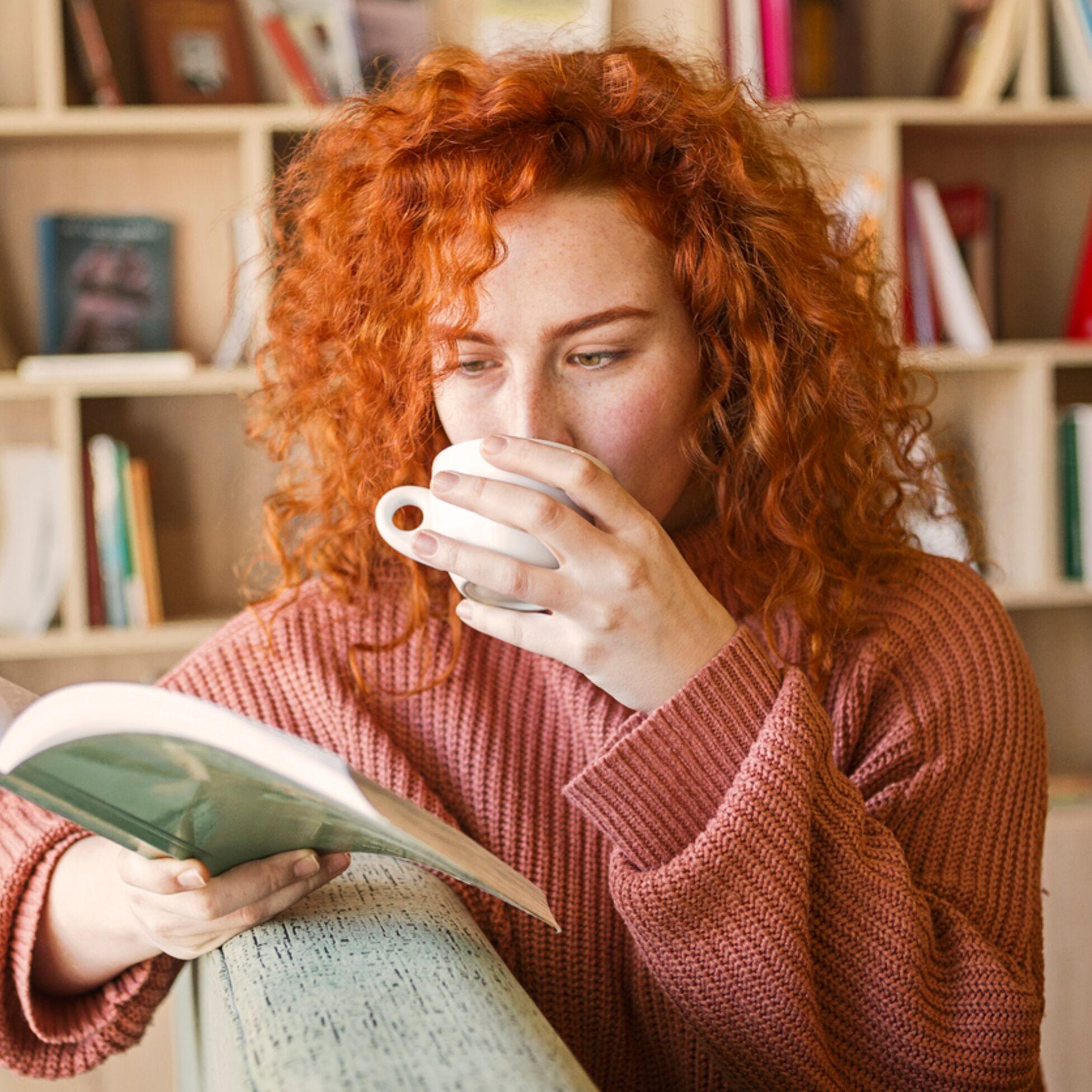 Frau liest Buch in gemütlicher Leseecke