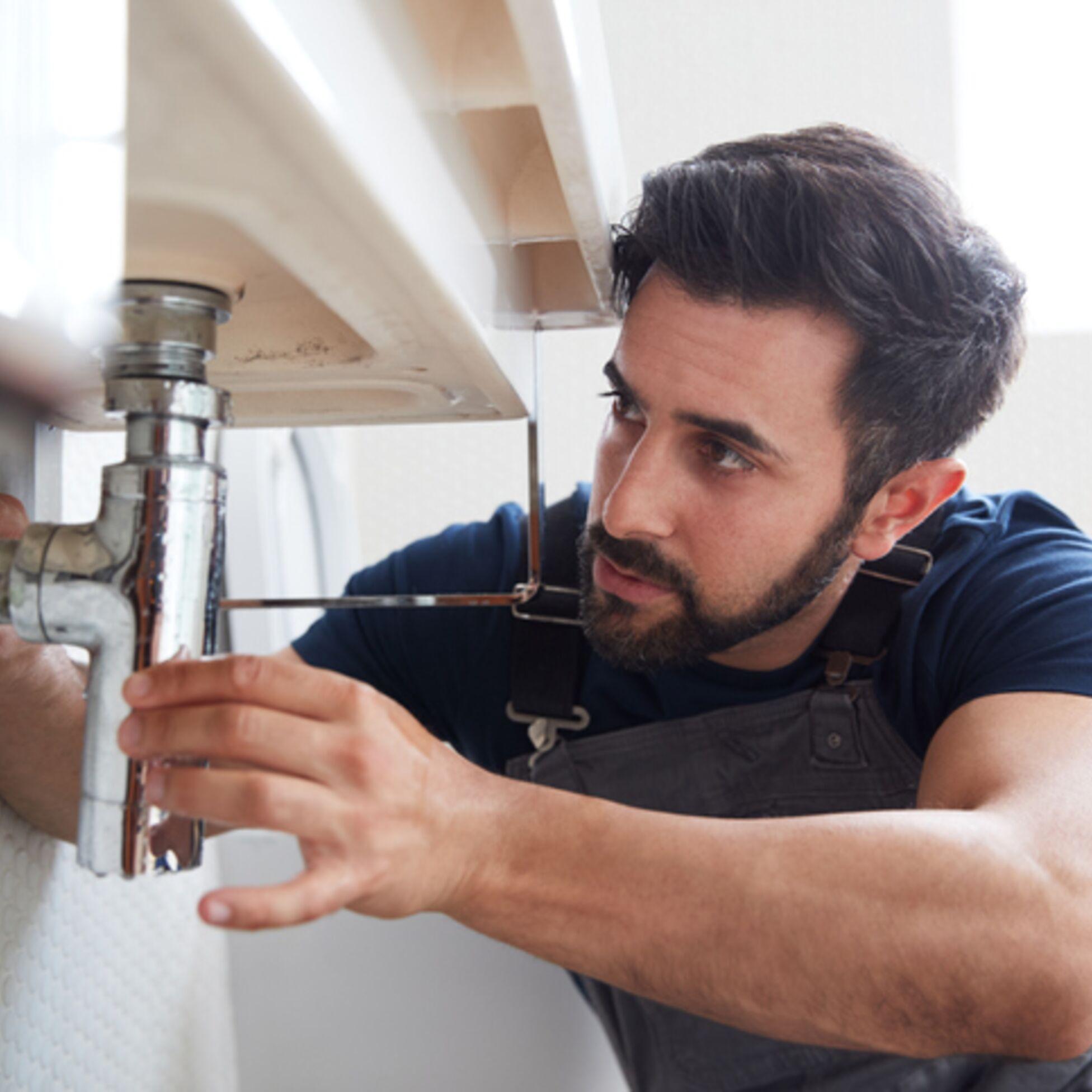 Hausmeister repariert ein Abflussrohr im Badezimmer