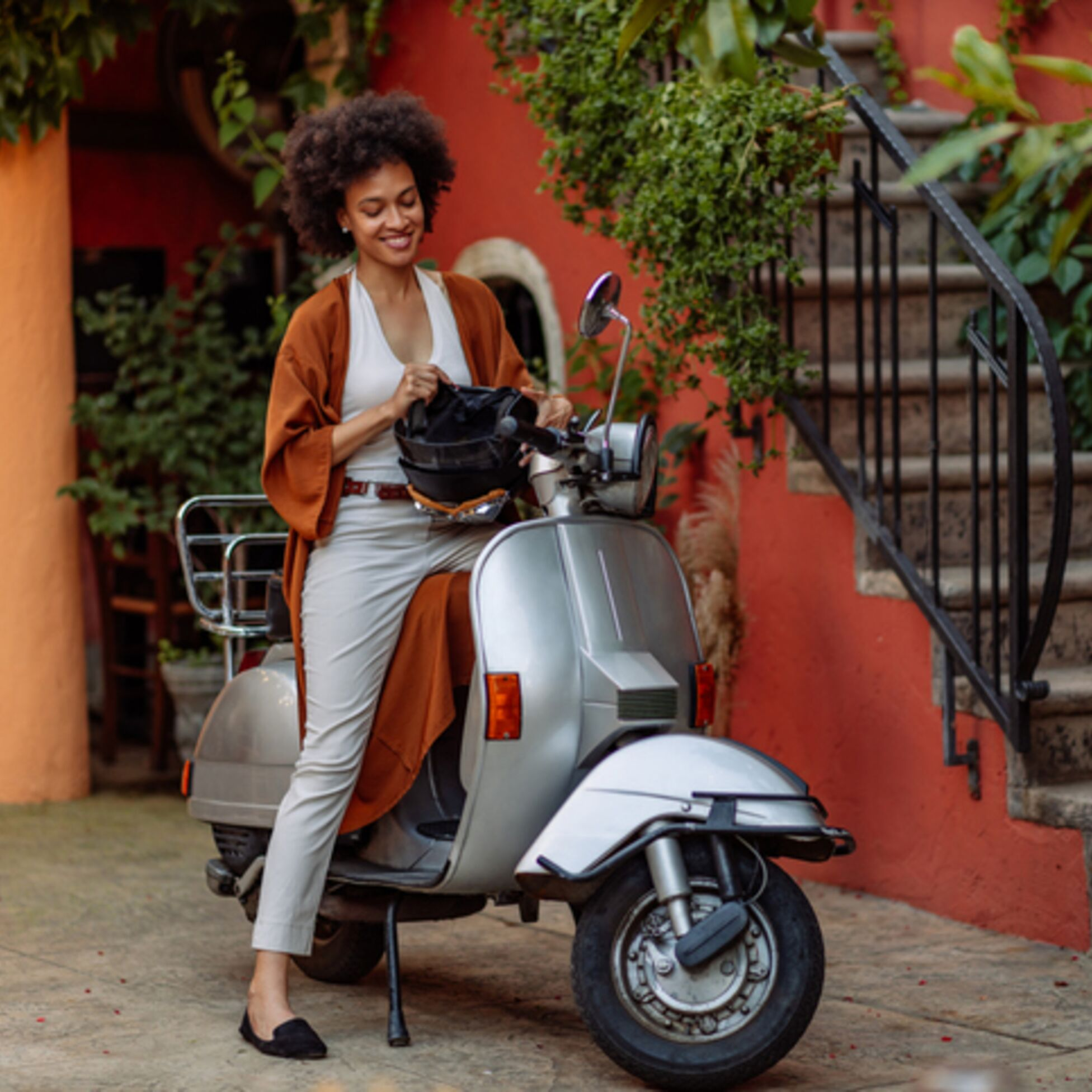 Frau sitzt auf Motorroller und hält Helm in der Hand
